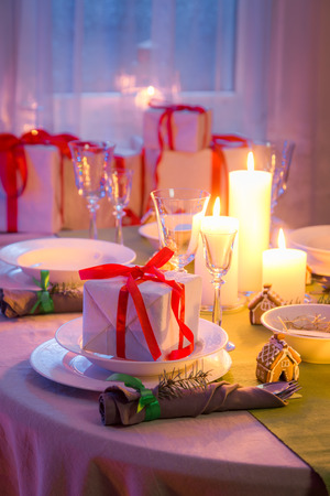 Beautiful Christmas table setting with candles and gingerbread in evening