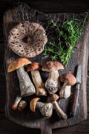 Various mushrooms and thyme on the old board Stock fotó