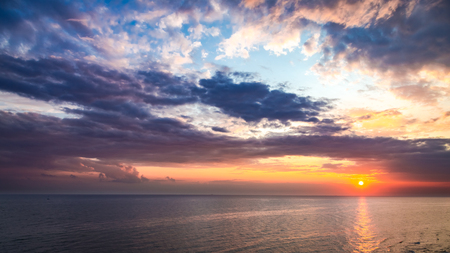 Wonderful sunset over calm sea in summer with sun beam Stock Photo