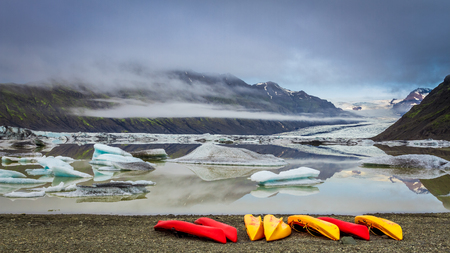 Kayaks and glacial lake in the cold mountains, Iceland
