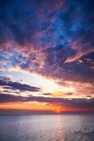 Wonderful dusk over calm ocean in summer with sun