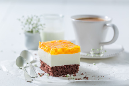 Sweet cake with jelly and peaches served with coffee