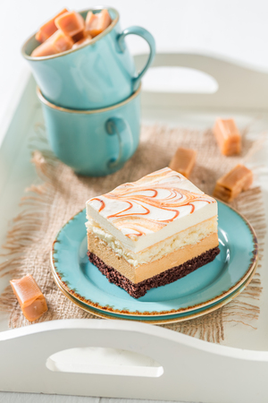 Delicious toffee cake with fudge bars on blue porcelain