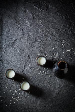 White sake in black ceramics on black rock Stock Photo