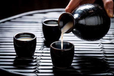 Pouring sake in to black ceramics on black table Stok Fotoğraf