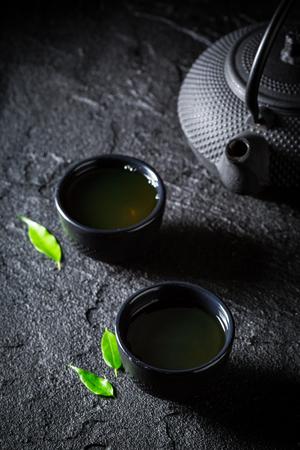 Fresh green tea in teacup on black rock
