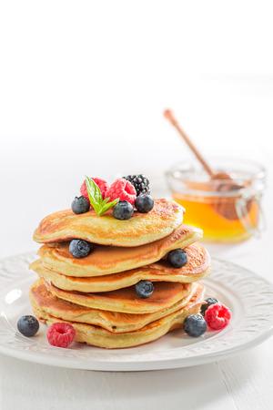 Close-up van Amerikaanse pannekoeken met ahornstroop en bessen