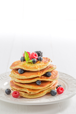 American pancakes with maple syrup and berries on white table
