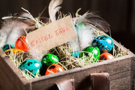 Eggs for Easter with hay and feathers in wooden box