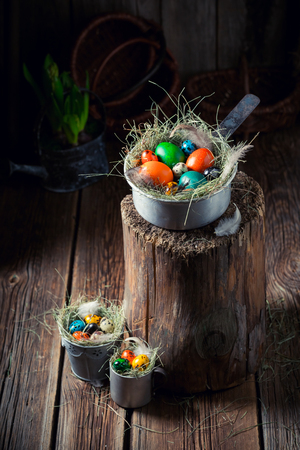 Various Easter eggs with hay and feathers on wooden shack
