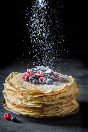 Falling powdered sugar on pancakes with berries