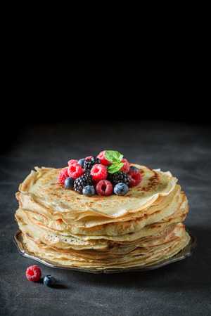 Pancakes with berries and powder sugar on black table Фото со стока