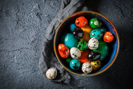 Closeup of colorful Easter eggs on black rock