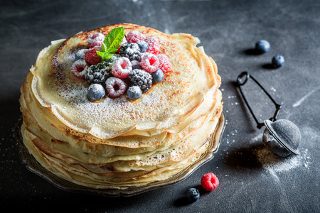 Stack of pancakes with powder sugar and berries