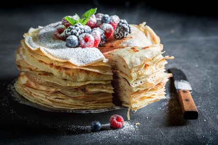 Piece of pancakes cake with berries and powdered sugar Reklamní fotografie - 92860200