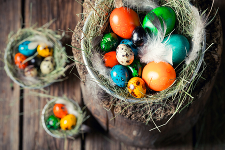 Colorful eggs for Easter in wooden small henhouse Stock Photo
