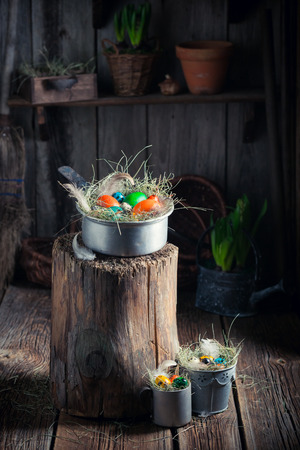 Various Easter eggs with hay and feathers in rural shack