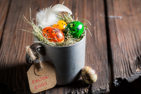 Various eggs for Easter with hay and feathers in mug