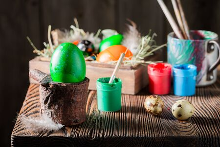 Decorating green Easter eggs with hay and feathers Stock Photo - 92859465