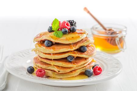 Pancake americani per la prima colazione di mattina su fondo bianco