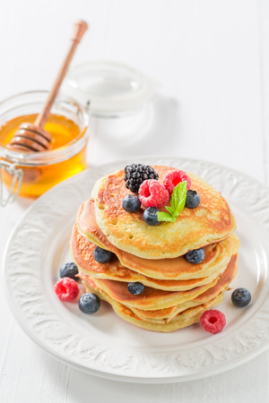 Golden american pancakes with maple syrup and berries