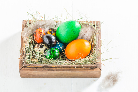 Easter eggs in wooden box on white table Stock Photo