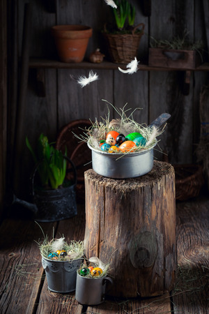 Falling feather on Easter eggs on wooden stump Stock Photo