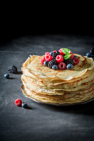 Big pancakes cake with fresh berries and mint