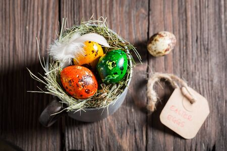 Colorful eggs for Easter with feathers on wooden table