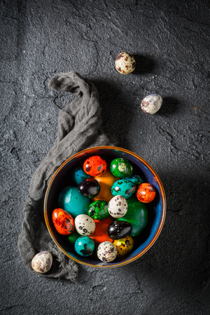 Colorful Easter eggs in blue bowl on black table