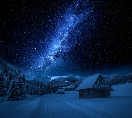 Milky way, cottages and snowy road at night, Tatra Mountains Banco de Imagens