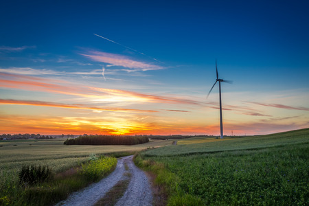 Stunning dusk over green field wind turbines in summer