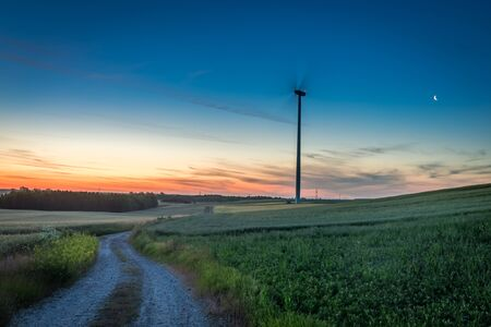 Stunning dusk over green field and wind turbines