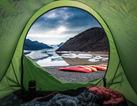 Camp by glacial lake in the mountains with kayak, Iceland Stockfoto