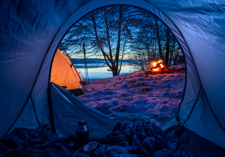Camp by the lake with campfire in winter at dusk Imagens