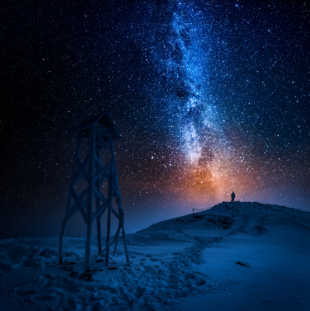 Man looking to the stars in the mountain in winter