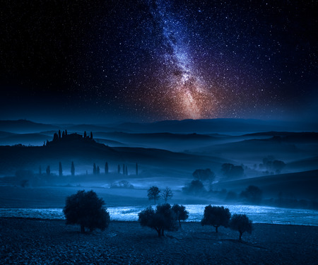 Milky way over fields in the valley in Tuscany, Italy 版權商用圖片