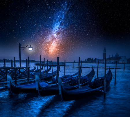 Swinging gondolas in Venice at night with stars Stock Photo
