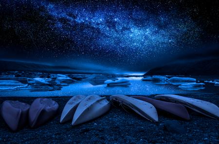 Milky way, kayaks and the glacier lake at night, Iceland