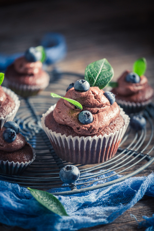Tasty muffin with fresh blueberries, cream and chocolate