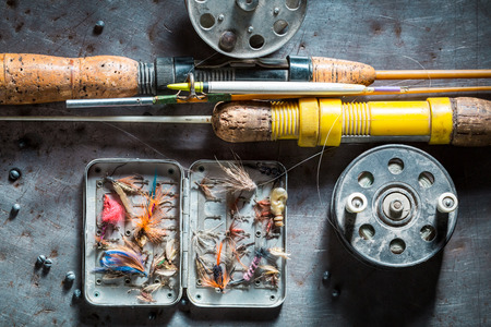 Vintage angler equipment with fishing flies and rods Stock Photo