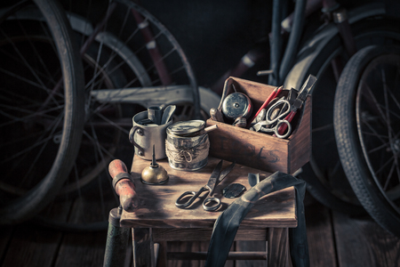 Old bicycle repair workshop with tools, wheels and tube Stock Photo