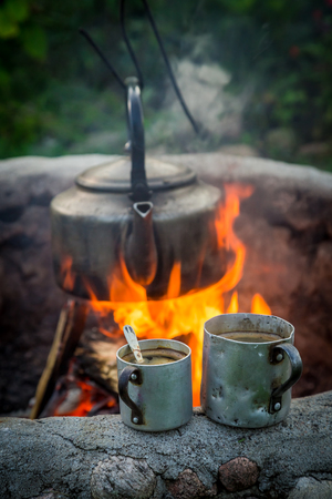 Freshly made coffee with kettle on bonfire