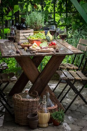 Garden table with snacks and wine in the evening