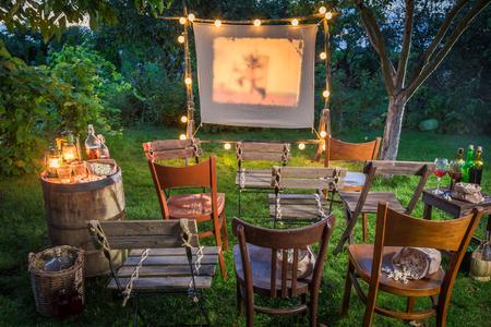 Zomerbioscoop met retro projector in de tuin Stockfoto