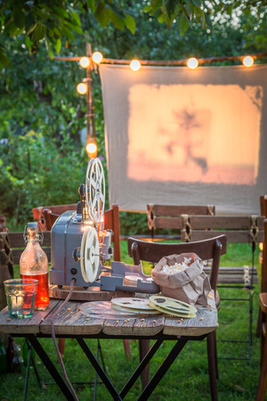 Open-air cinema with retro projector in the garden Archivio Fotografico