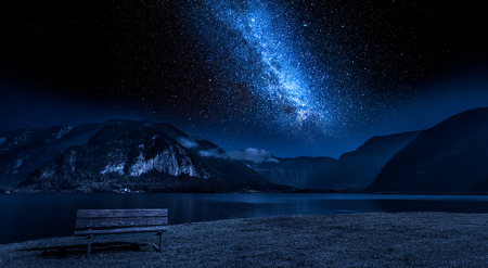 Wooden bench and lake mountain between at night with stars