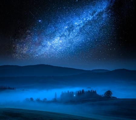 Milky way and small farm on field at night, Italy