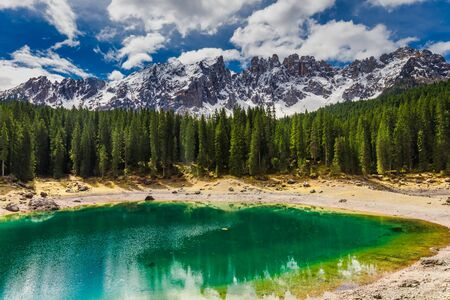 Green mountain Carezza lake in Dolomites, Italy, Europe