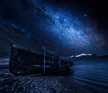 Milky way and old ship wreck at night, Iceland Stock Photo
